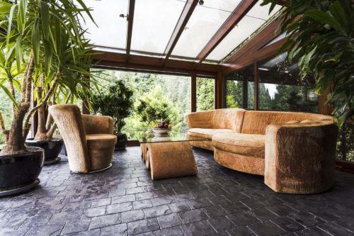 Luxus-Kaltwintergarten mit braunen Sofas, Glastisch und großen Pflanzen; alles direkt am Haus
