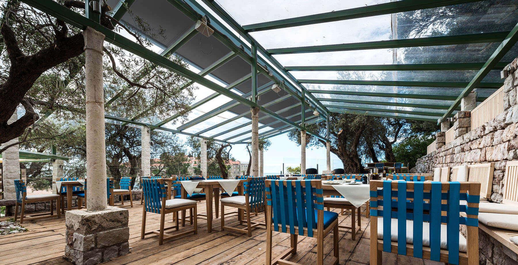 Sonnenschutz-Vorrichtung auf der Terrassendach, dass über den Außenbereich eines rustikalen Restaurants montiert ist