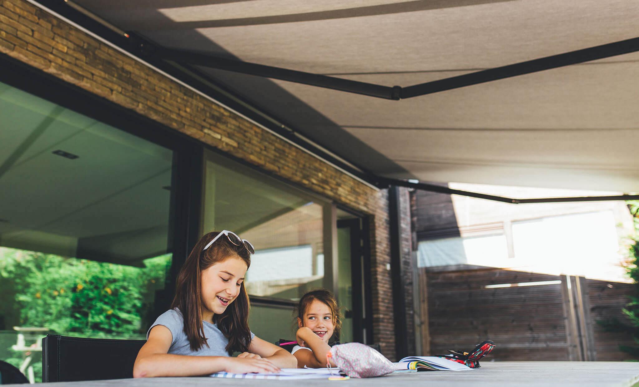 Markise über Kinder, die auf der Terrasse ihre Hausaufgaben machen