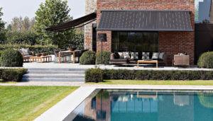 Zwei Markisen an einer Terrasse mit großem Garten und Pool, eine davon seitlich, die andere frontal zum Pool