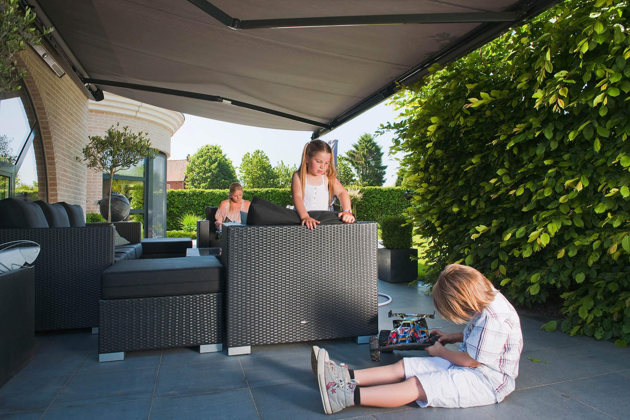 Zwei Kinder und Mutter auf Terrasse unter einer Gelenkarm-Markise