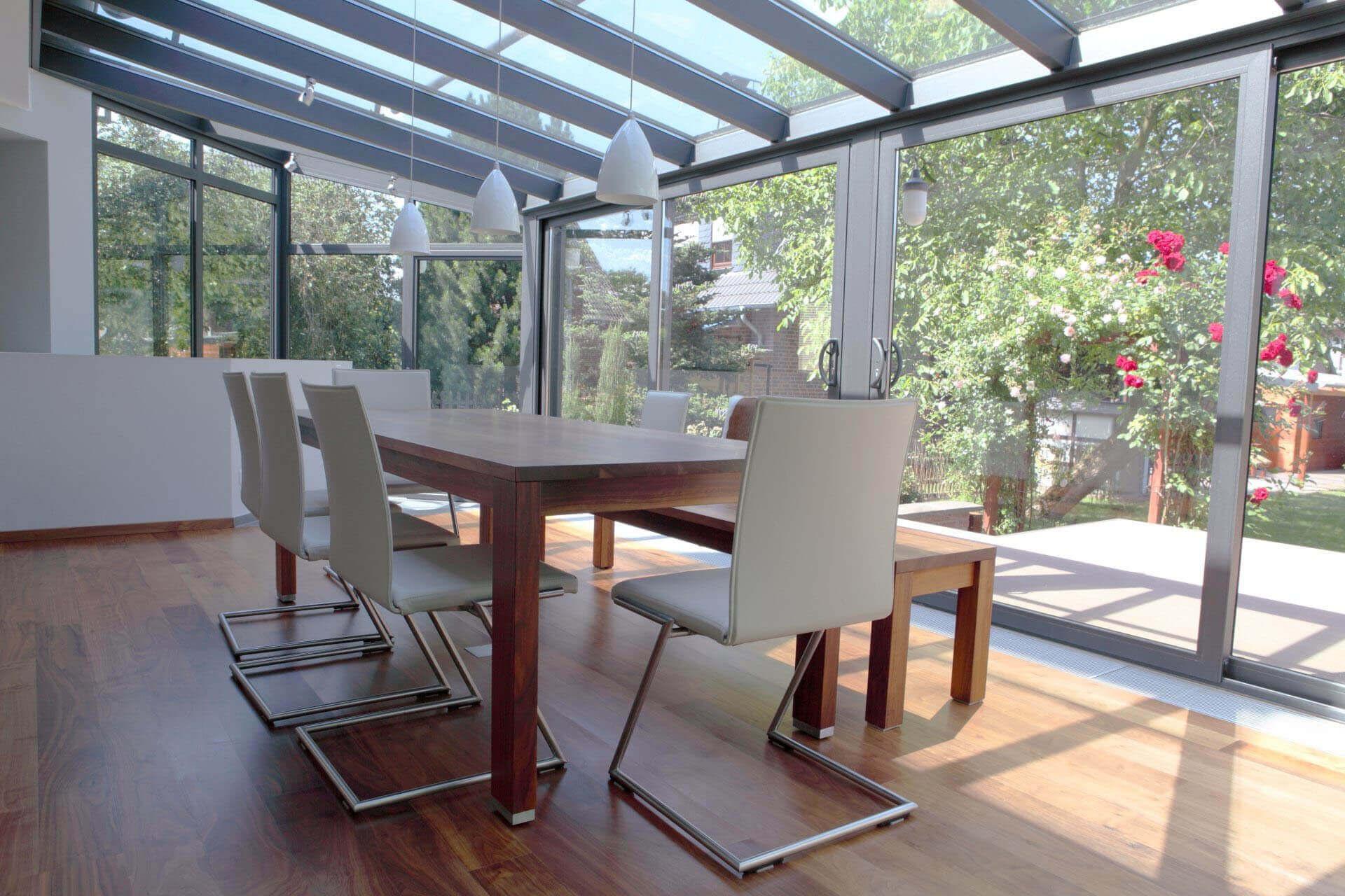 Kaltwintergarten mit Tisch und Stühlen direkt am Haus; 2 Schiebetüren zum Öffnen vorhanden, dazu Festelemente seitlich