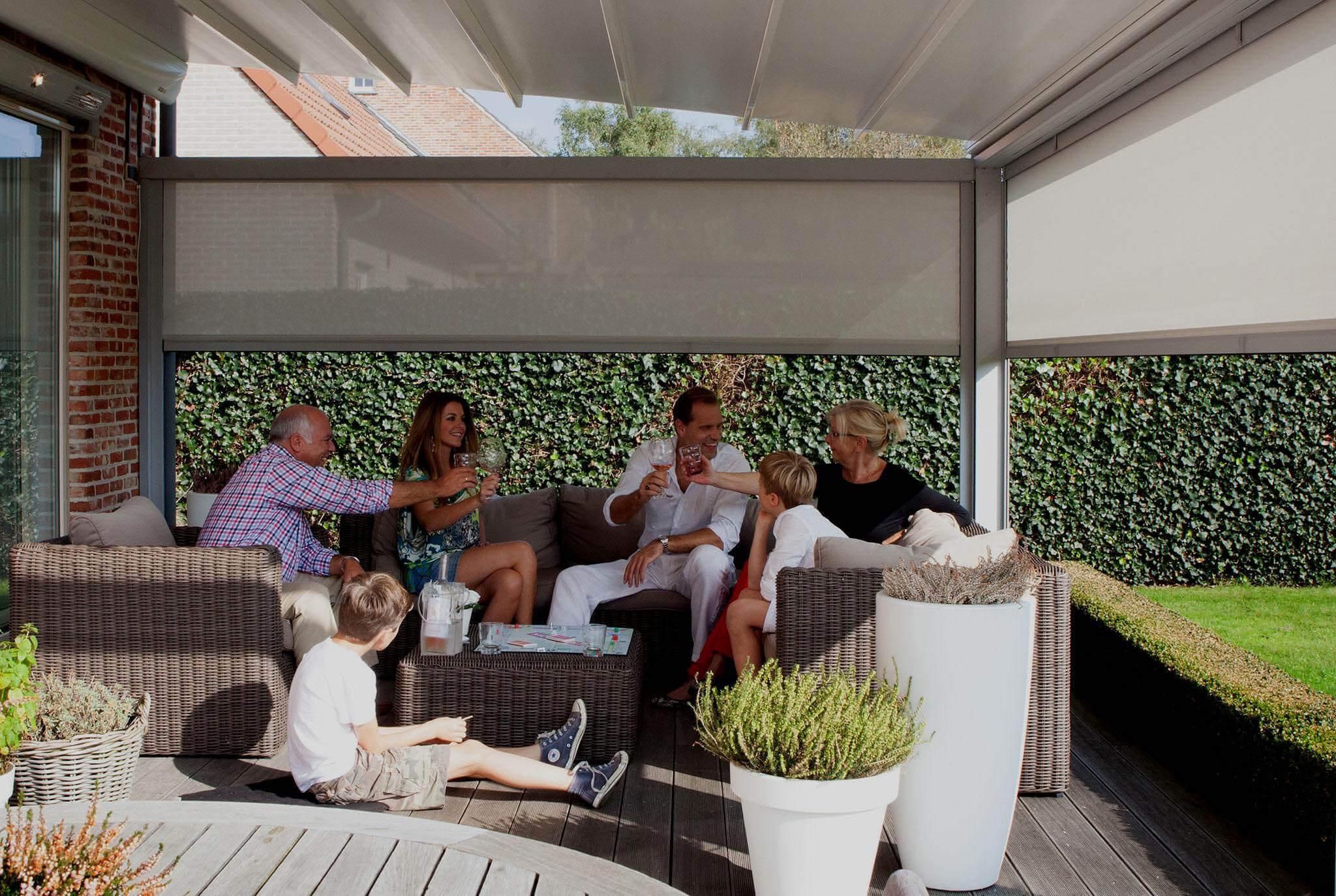 Familie auf Terrasse mit Rattansitzgelegenheiten unter Faltdach-Überdachung