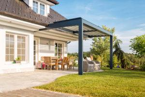 Relaxdach Lamellen-Terrassenüberdachung am Haus über der Terrasse mit Tische, Stühlen und Sesseln direkt vor dem Garten