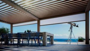 Überdachung mit Lamellen mit Blick auf Meer; unter der Überdachung ein Holztisch und blaue Stühle