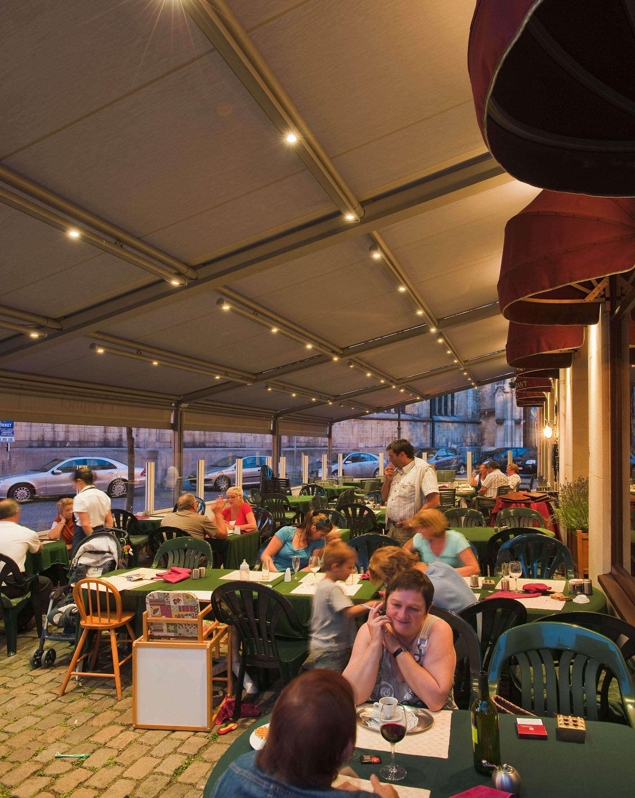 Pergola-Überdachung mit Beleuchtung am Tuch über dem Außenbereich eines Restaurants oder Bistros angebracht