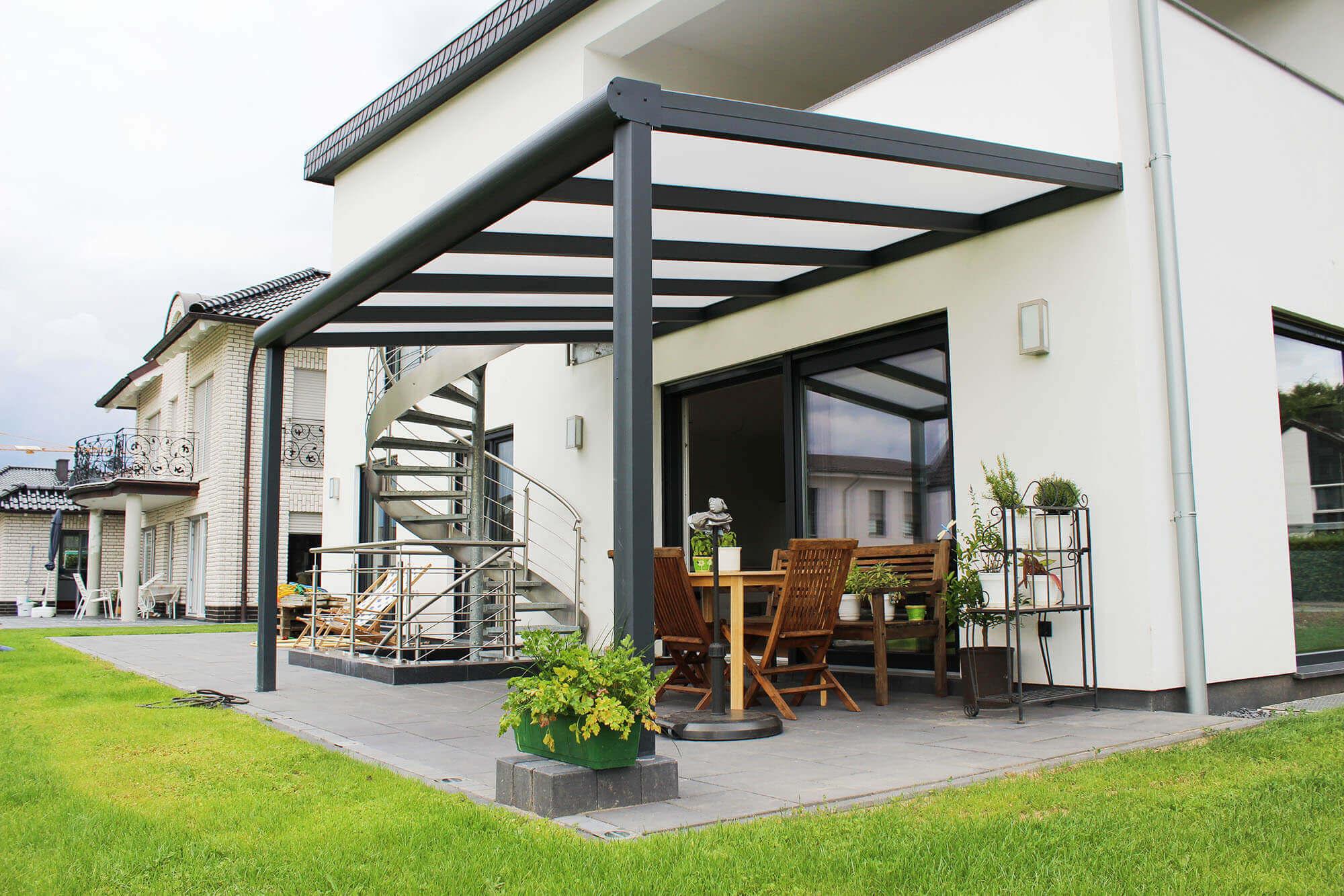 Terrassenüberdachung aus Aluminium mit milchigem Glas an weißem Haus und sich drehender Treppe daneben