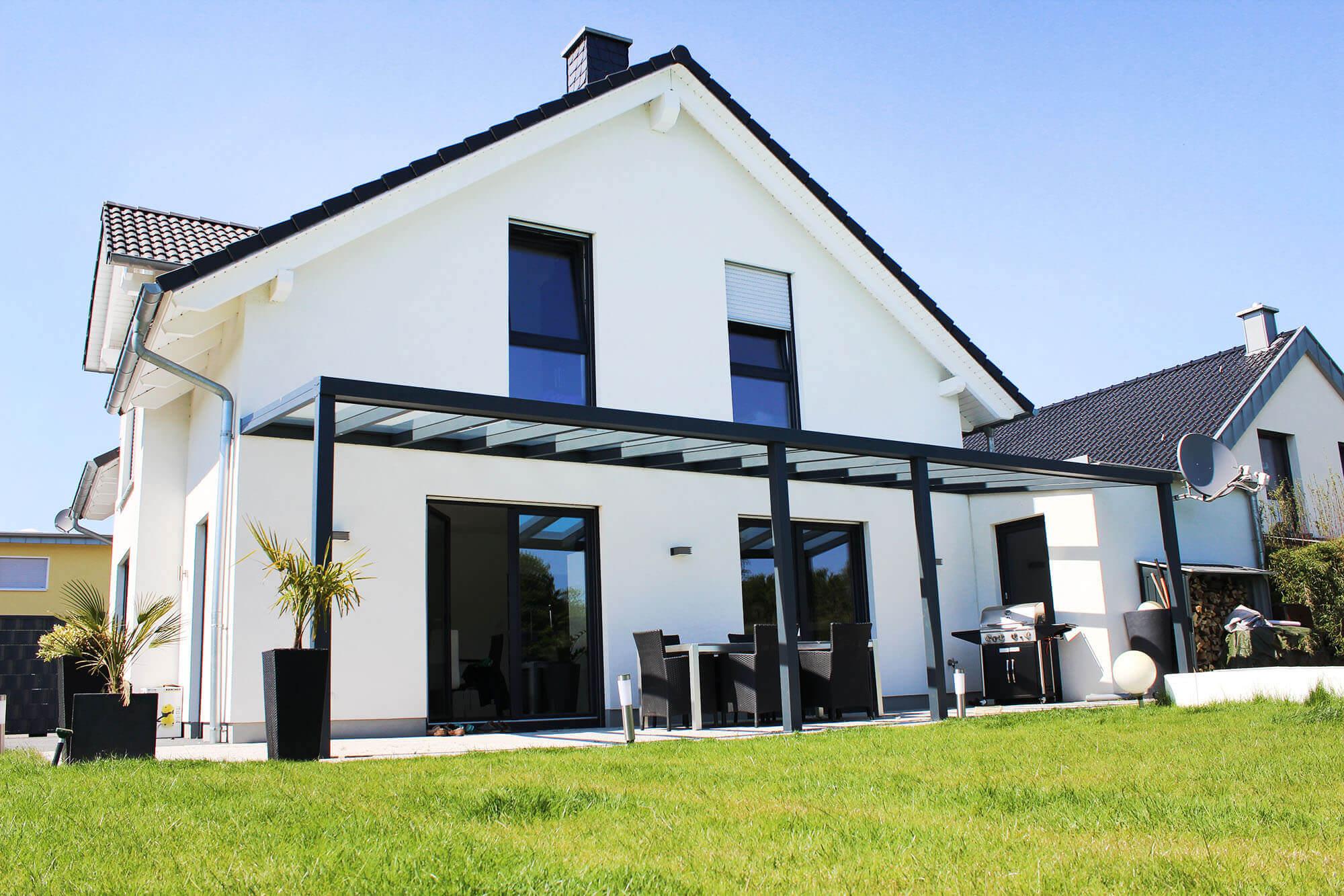 Terrassenüberdachung schwarz mit durchsichtigem VSG-Glas an weißem Haus mit 2 Stützen in der Mitte