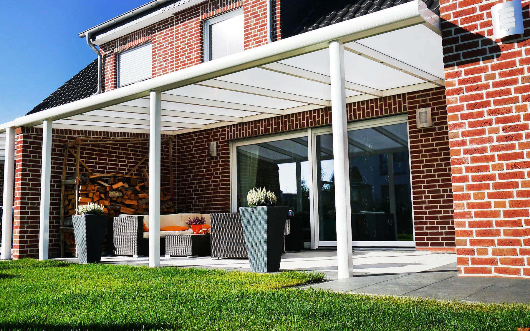 Weiße Terrassenüberdachung mit milchigem Polycarbonat-Glas an rot verklinkertem Haus