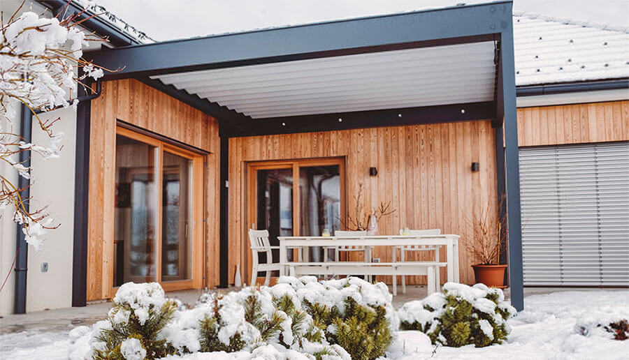 Terrassenüberdachung aus schwarzem Aluminium im Schnee
